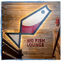 back lit wooden sign of Big Fish Lounge's logo