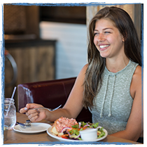 Female smiling while enjoying a lobster roll