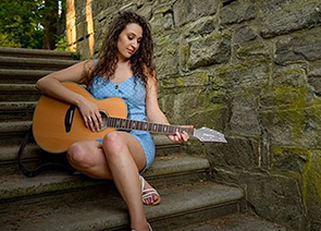 A girl on stone steps holding a guitar.