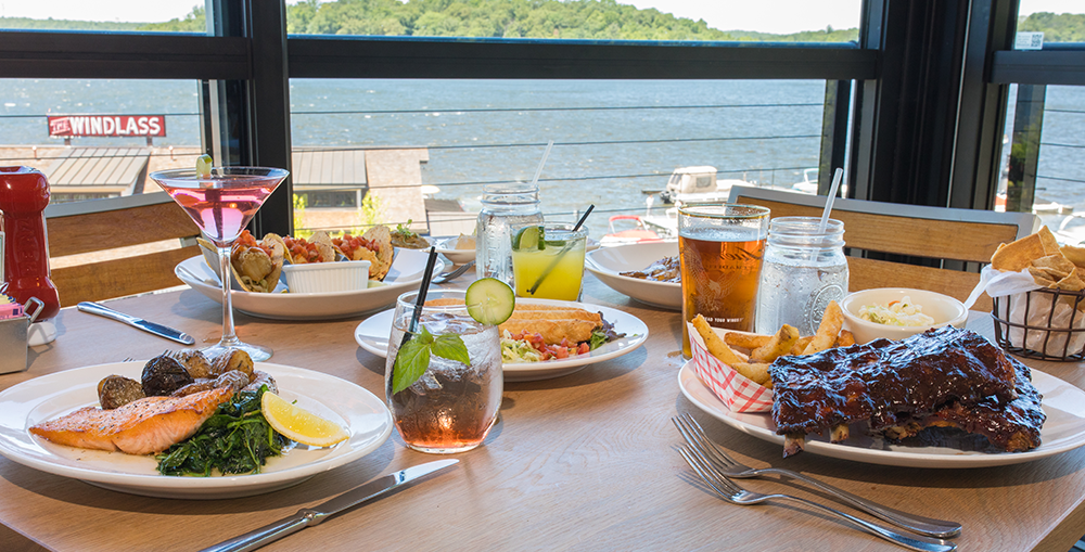 Table set with drinks and various dishes with a view of Lake Hopatcong